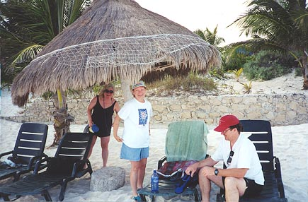 A 'palapa,' or thatched hut, offers shade on the white sand beach.