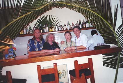 Jim, Deborah, Liz and Dennis pose behind the restaurant bar decorated with crossed palms.